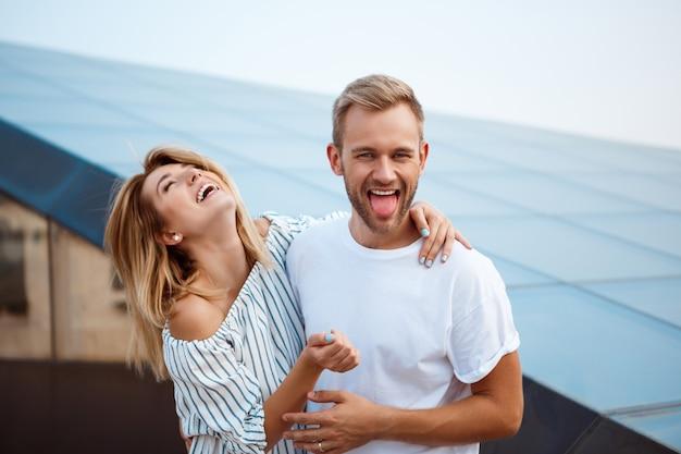 Giovani belle coppie che sorridono, abbracciando, camminando intorno alla città Foto Gratuite
