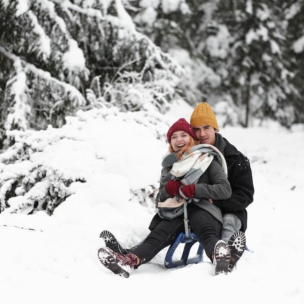 Giovani belle coppie divertendosi seduta sulla slitta Foto Gratuite