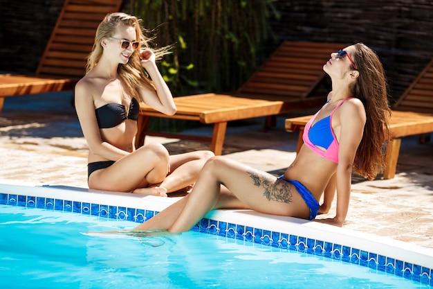 Giovani belle donne che sorridono, prendendo il sole, rilassandosi vicino alla piscina Foto Gratuite