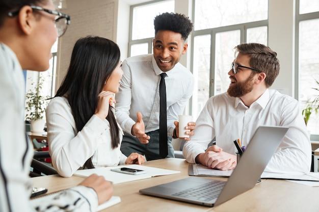 Giovani colleghi positivi cherful che per mezzo del computer portatile. Foto Gratuite