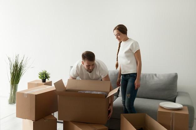 Giovani coniugi che trasportano scatole trasferirsi in un nuovo appartamento Foto Gratuite