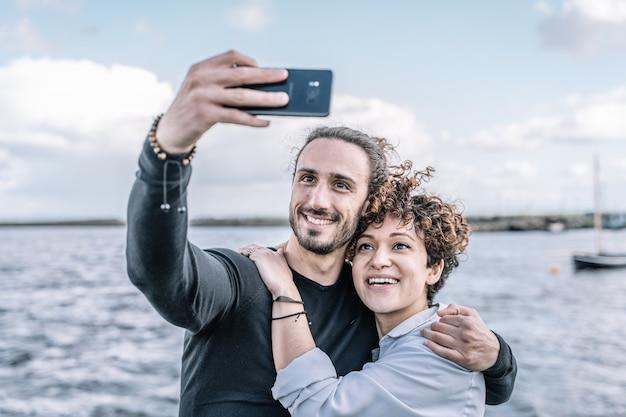 Giovani coppie abbracciate dalla spalla che fa un selfie con il porto e il mare sfuocato Foto Premium
