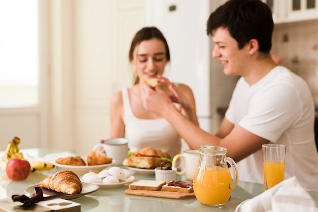 Giovani coppie adorabili che servono insieme prima colazione Foto Gratuite