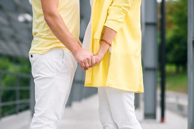 Giovani coppie adorabili nel tenersi per mano luminoso dei vestiti Foto Premium