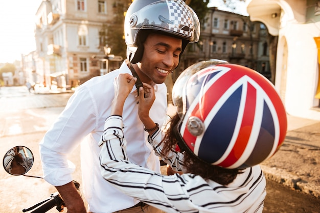 Giovani coppie africane in caschi da moto sulla strada Foto Gratuite
