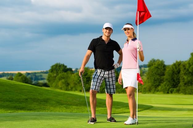 Giovani coppie allegre che giocano a golf su un corso Foto Premium