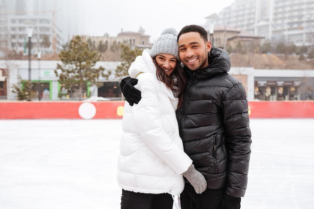Giovani coppie amorose allegre che pattinano alla pista di pattinaggio sul ghiaccio all'aperto. Foto Gratuite