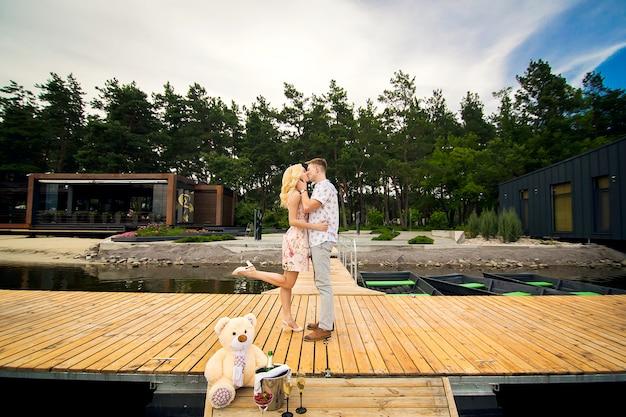 Giovani coppie amorose baci su un molo di legno. lovestory sul molo Foto Premium