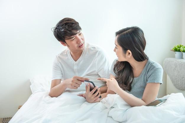 Giovani coppie asiatiche arrabbiate o combattimento di matrimonio per un telefono cellulare a casa. smart phone caucasico geloso della tenuta della donna e mostrare messaggio a suo marito con discussione e moto insoddisfatto. Foto Premium
