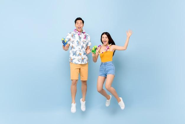Giovani coppie asiatiche in abiti estivi con pistole ad acqua che saltano per il festival di songkran in thailandia e sud-est asiatico Foto Premium