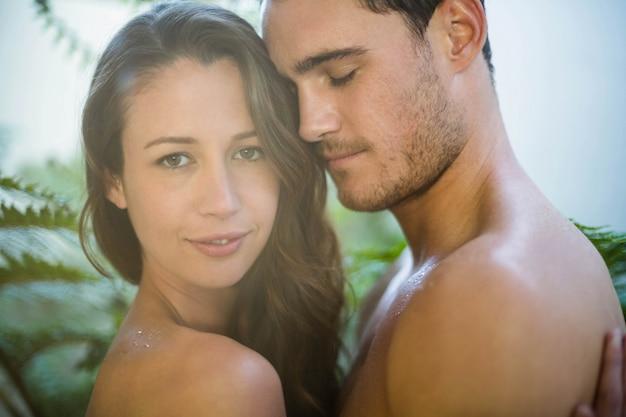 Giovani coppie che abbracciano appassionatamente in giardino Foto Premium