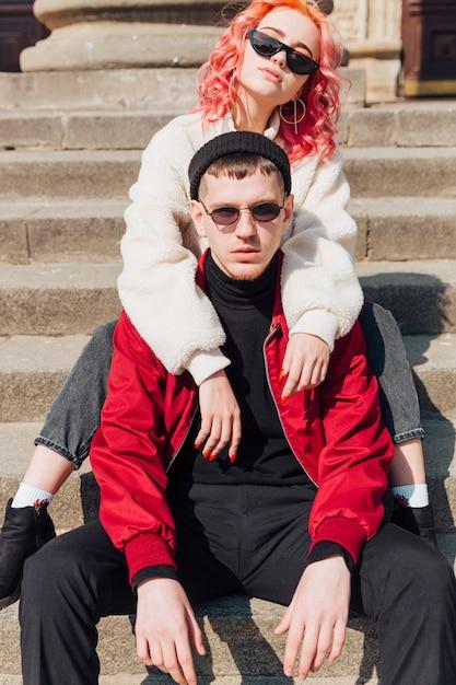 Giovani coppie che abbracciano seduti sulle scale Foto Gratuite