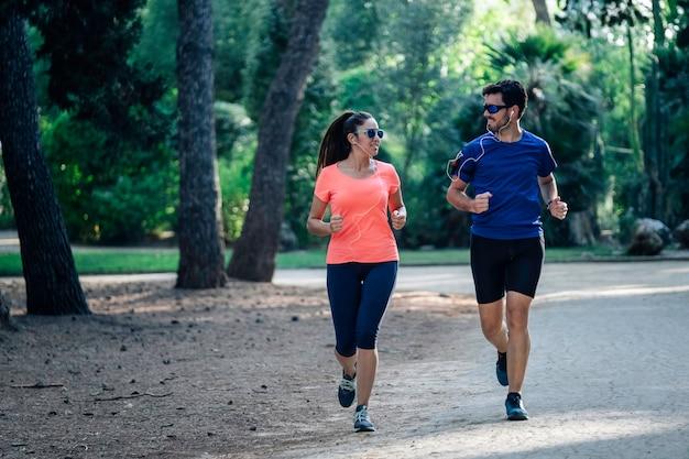 Giovani coppie che attraversano il parco e che ascoltano la musica. concetto di vita sana. Foto Premium