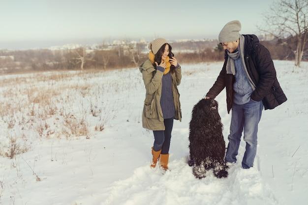Giovani coppie che camminano con un cane in un giorno di inverno Foto Gratuite