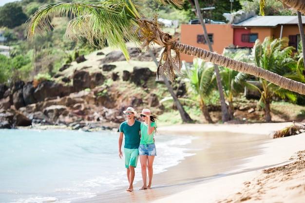 Giovani coppie che camminano sulla spiaggia tropicale della baia di carlisle Foto Premium