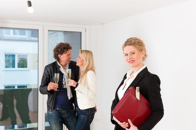 Giovani coppie che cercano bene immobile con l'agente immobiliare femminile Foto Premium