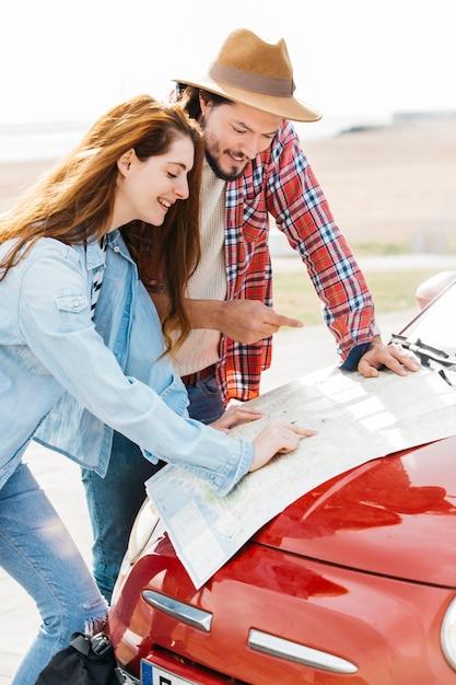 Giovani coppie che esaminano il programma di strada sull'automobile Foto Gratuite