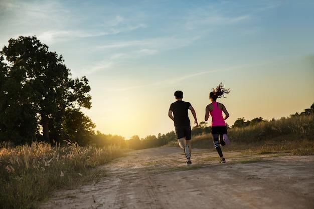 Giovani coppie che funzionano alla traccia della foresta Foto Premium