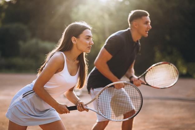 Giovani coppie che giocano a tennis alla corte Foto Gratuite