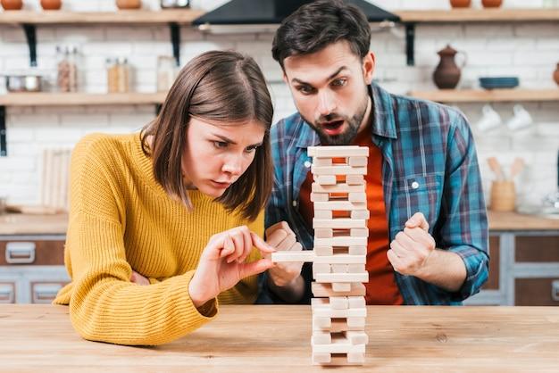Giovani coppie che giocano il blocco impilato di legno sul tavolo Foto Gratuite