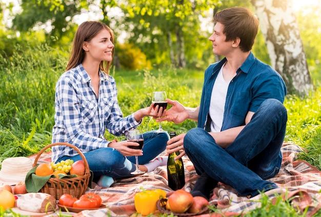Giovani coppie che hanno picnic con cibo e vino Foto Gratuite