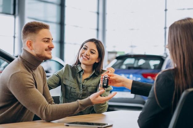 Giovani coppie che parlano con un addetto alle vendite in una sala d'esposizione dell'automobile Foto Gratuite