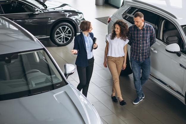 Giovani coppie che parlano con un venditore in una sala d'esposizione dell'automobile Foto Gratuite