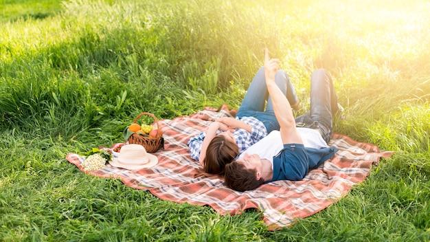 Giovani coppie che riposano sulla coperta nella foresta Foto Gratuite