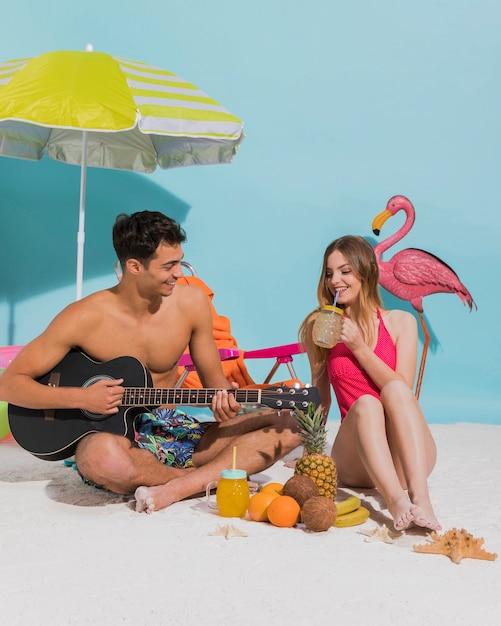 Giovani coppie che riposano sulla sabbia in studio Foto Gratuite