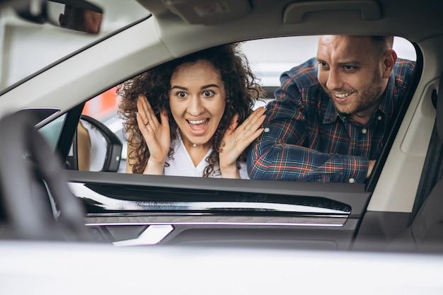 Giovani coppie che scelgono un'automobile in una stanza di manifestazione di automobile Foto Gratuite