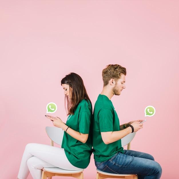 Giovani coppie che si siedono di nuovo alla parte posteriore facendo uso di whatsapp sullo smartphone Foto Gratuite