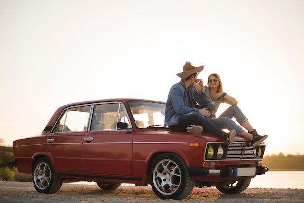 Giovani coppie che si siedono su un'auto d'epoca Foto Gratuite