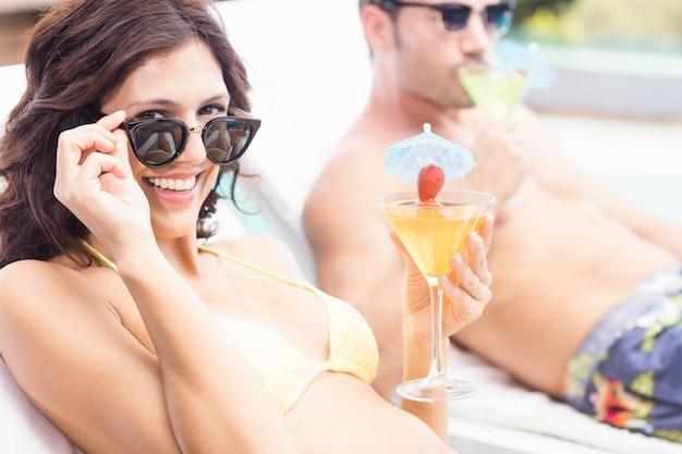 Giovani coppie che si siedono sui lettini dalla piscina Foto Premium