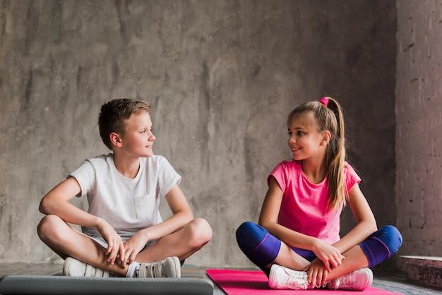 Giovani coppie che si siedono sulla stuoia di esercitazione con le sue gambe attraversate che esaminano macchina fotografica contro il muro di cemento Foto Gratuite