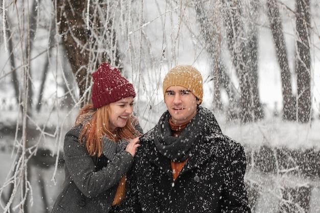 Giovani coppie che sorridono e che giocano con la neve Foto Gratuite