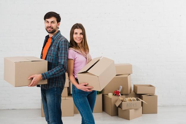 Giovani coppie che stanno di nuovo alla parte posteriore che tiene le scatole di cartone a disposizione Foto Gratuite