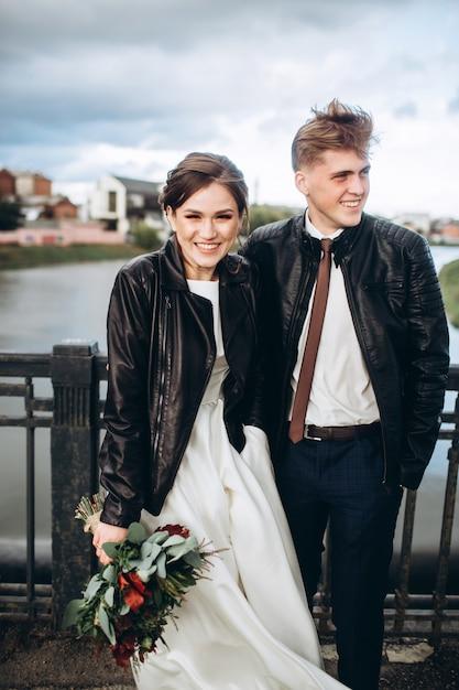 Giovani coppie che stringono a sé su un ponte sopra un fiume. gli sposi in giacche di pelle. coppia di innamorati in una fredda giornata autunnale a spasso per la città. panorama della città con un cielo tempestoso Foto Premium