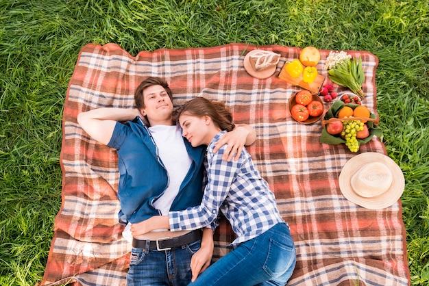 Giovani coppie che stringono a sé sulla coperta durante il picnic Foto Gratuite