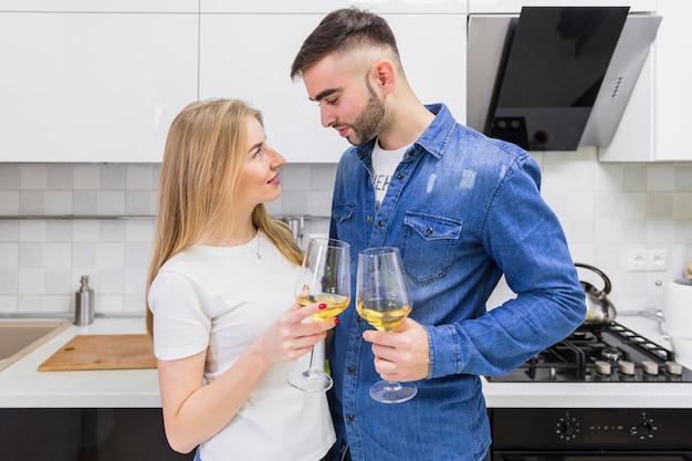 Giovani coppie clanging bicchieri di vino in cucina Foto Gratuite