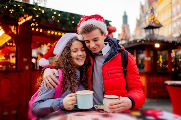 Giovani coppie con le bevande sul mercato di natale a wroclaw, polonia Foto Premium