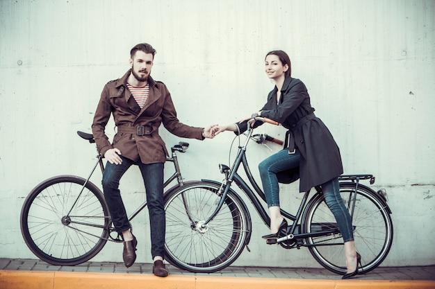Giovani coppie con una bicicletta di fronte alla città Foto Gratuite