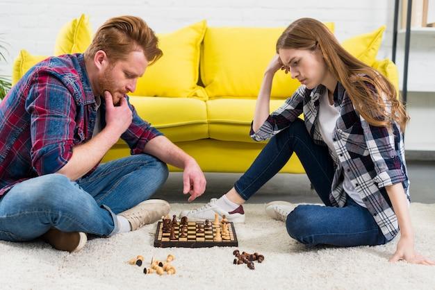 Giovani coppie contemplate che esaminano il gioco di scacchi nel salone Foto Gratuite