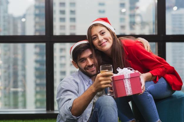 Giovani coppie divertendosi e innamorate dei contenitori di regalo della tenuta della festa di natale che portano il cappello di santa Foto Premium