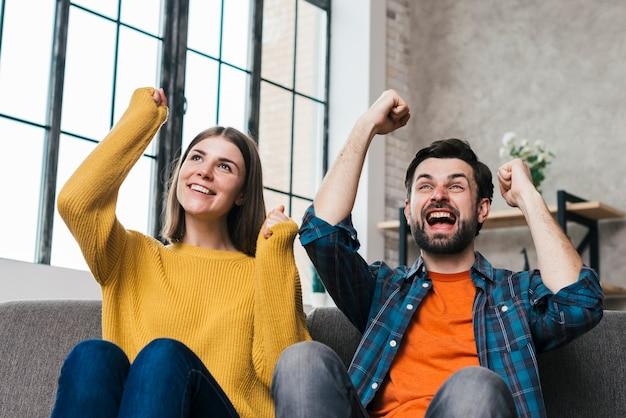 Giovani coppie emozionanti che si siedono sul sofà che incoraggiano con la gioia a casa Foto Gratuite