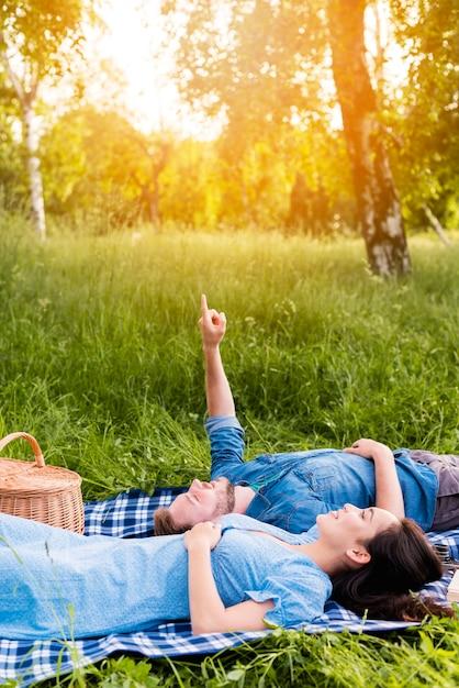 Giovani coppie felici che esaminano cielo mentre trovandosi sulla coperta in natura Foto Gratuite