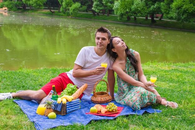 Giovani coppie felici che fanno un picnic e che si rilassano all'aperto Foto Premium