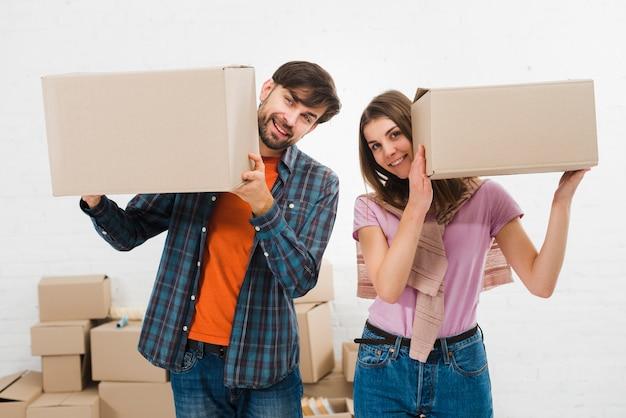 Giovani coppie felici che giudicano le scatole di cartone a disposizione Foto Gratuite