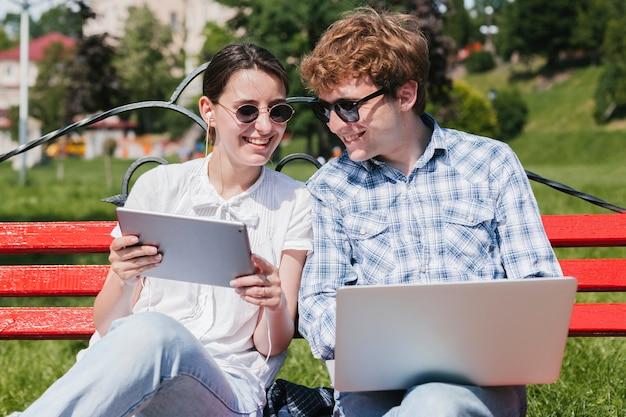 Giovani coppie felici che lavorano nel parco Foto Gratuite