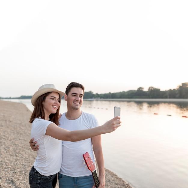 Giovani coppie felici che prendono i selfies al tramonto Foto Gratuite