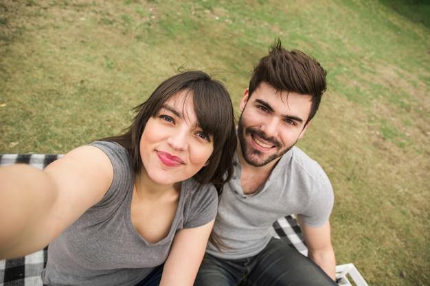 Giovani coppie felici che prendono selfie nel parco Foto Gratuite